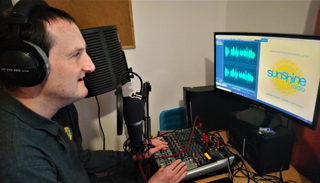 Programme Controller Steve Ledbrook editing audio messages at home.